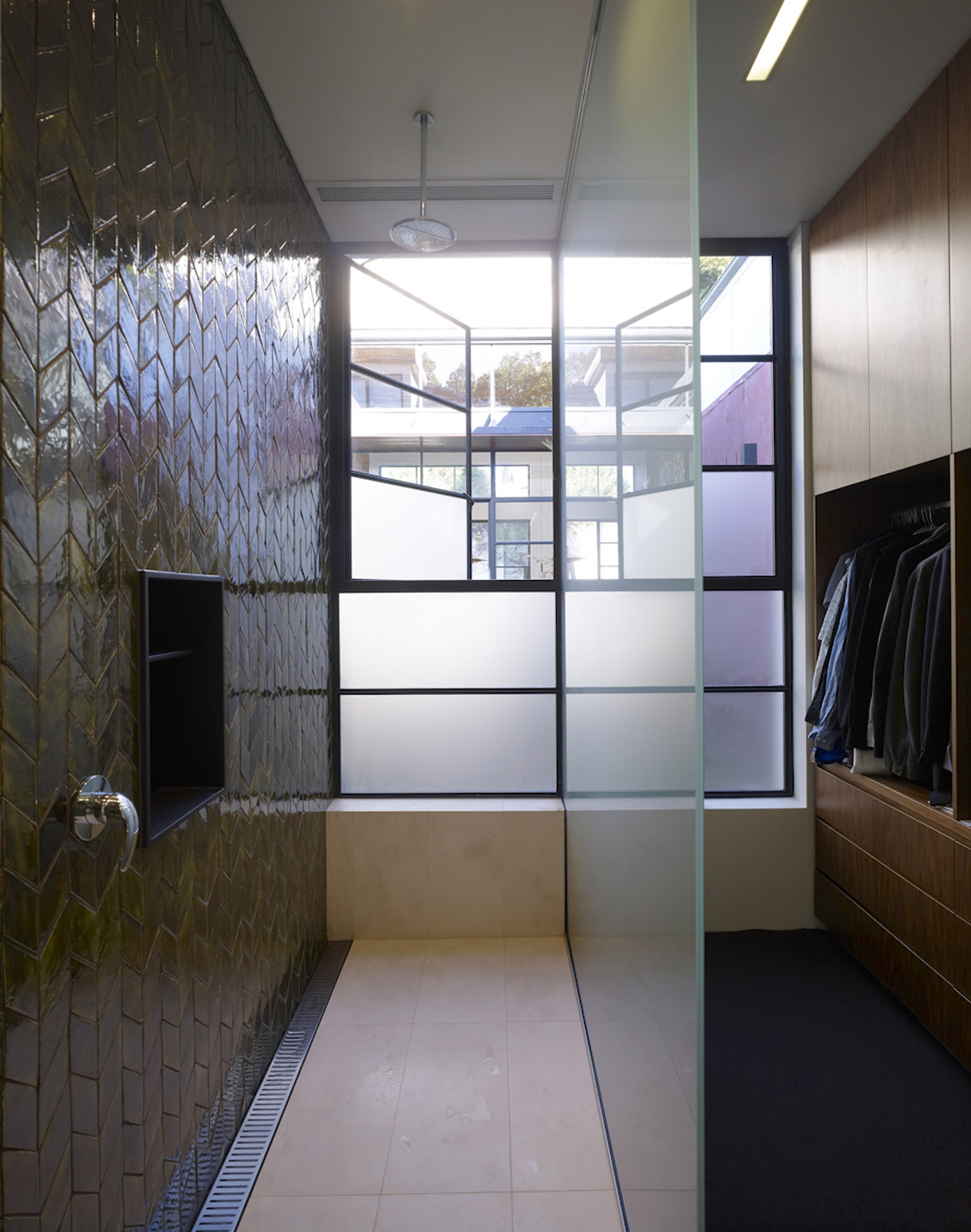 Smee Schoff House by award winning Sydney residential architecture firm Sam Crawford Architects. Light-filled bathroom and walk-in robe divided by frosted glass screen