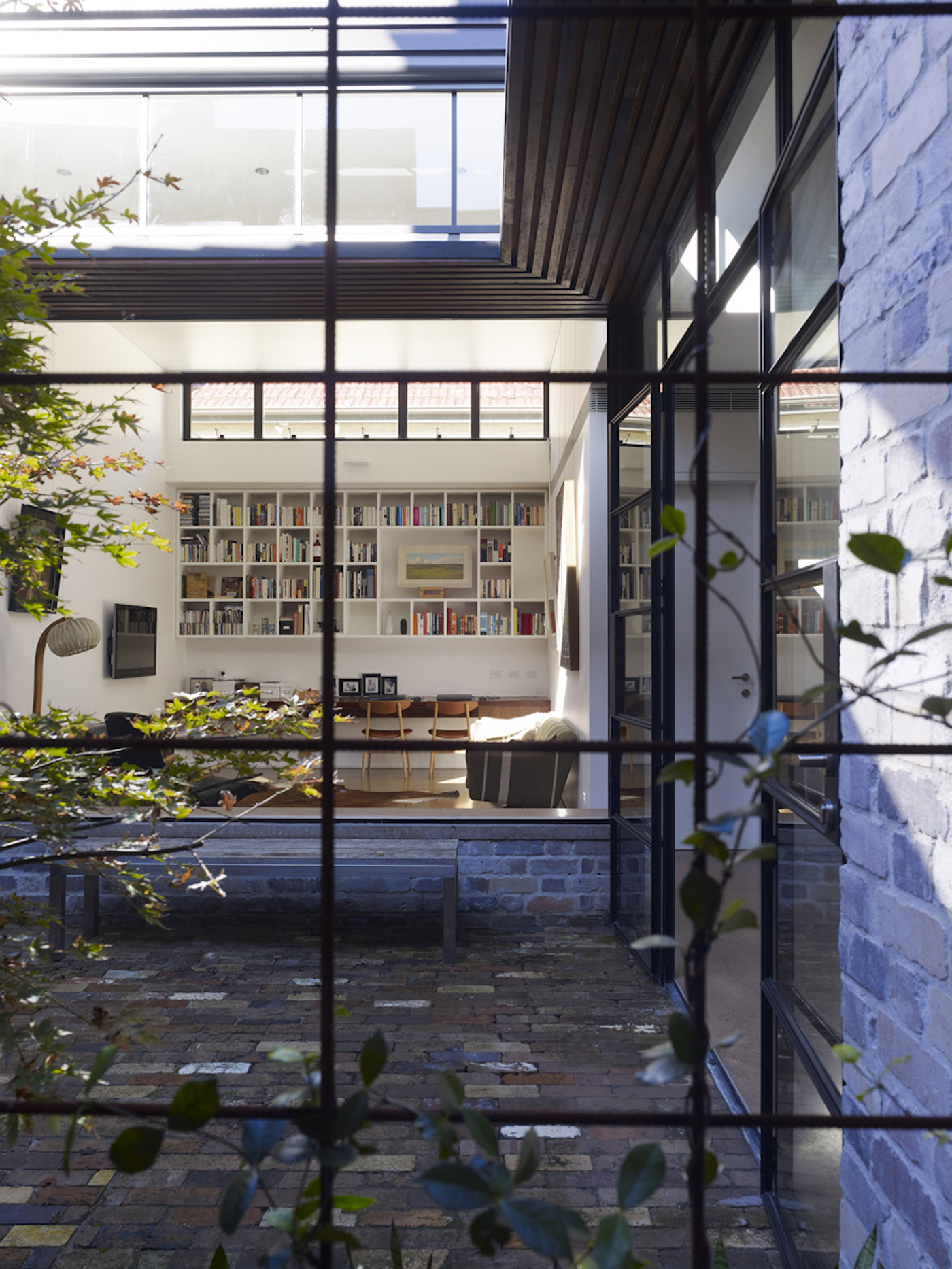 Smee Schoff House by award winning Sydney residential architecture firm Sam Crawford Architects. View to double-height living space connected by central garden courtyard