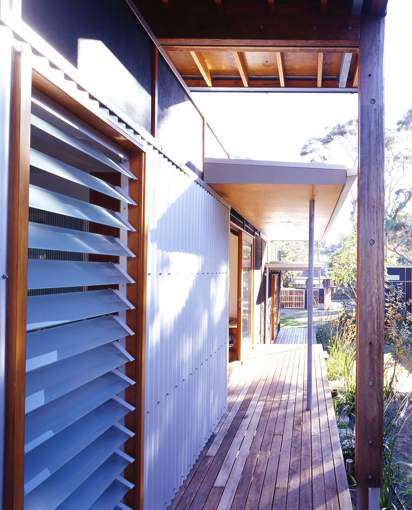 Bundeena Beach House by Sydney award winning residential architecture firm Sam Crawford Architects. Timber decking with white corrugated iron cladding with timber framed louver windows.