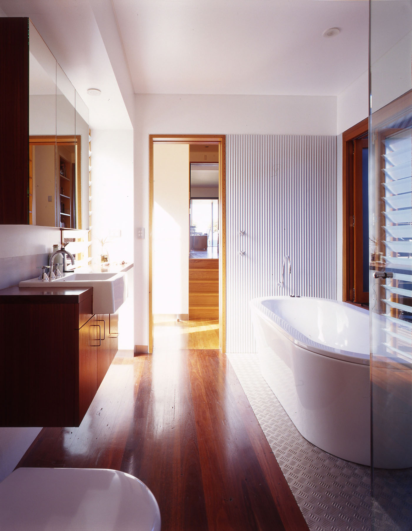 Bundeena Beach House by Sydney award winning residential architecture firm Sam Crawford Architects. View to light-filled bathroom with stamp and corrugated steel.