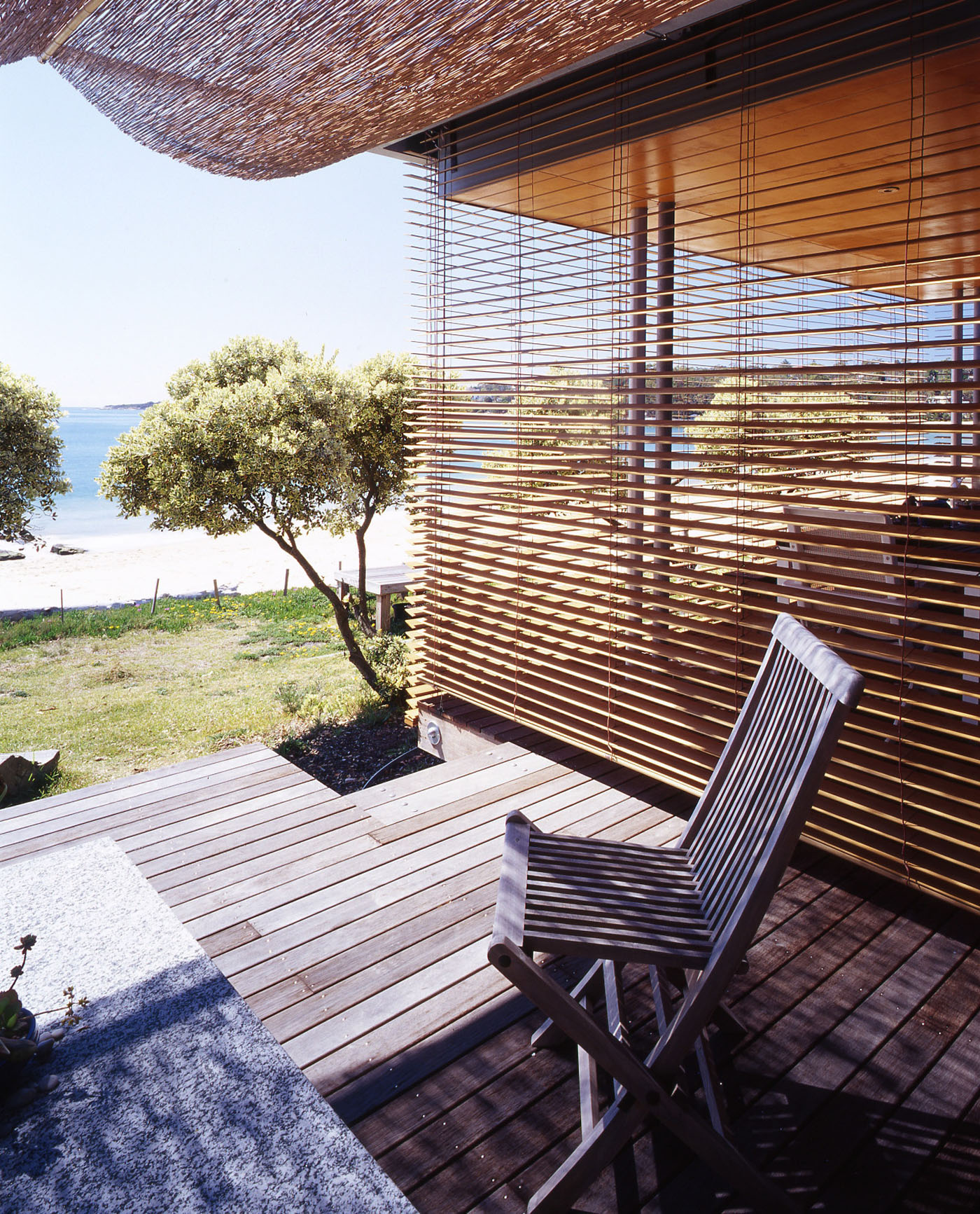 Bundeena Beach House by Sydney award winning residential architecture firm Sam Crawford Architects. View to open deck with timber louver infiltrating north eastern sunlight.