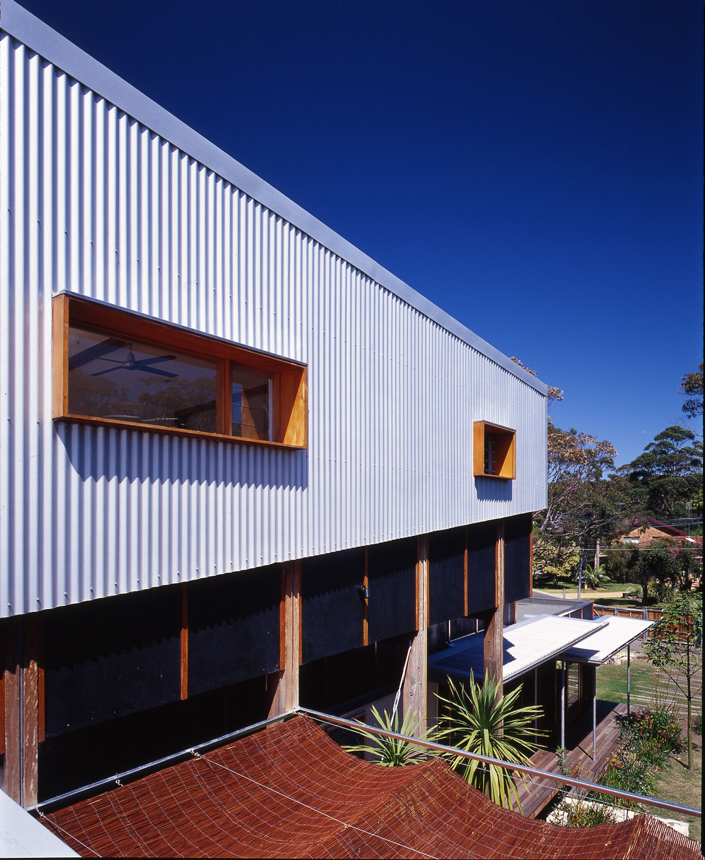 Bundeena Beach House by Sydney award winning residential architecture firm Sam Crawford Architects. View from first floor to external corrugated steel cladding and timber framed windows.