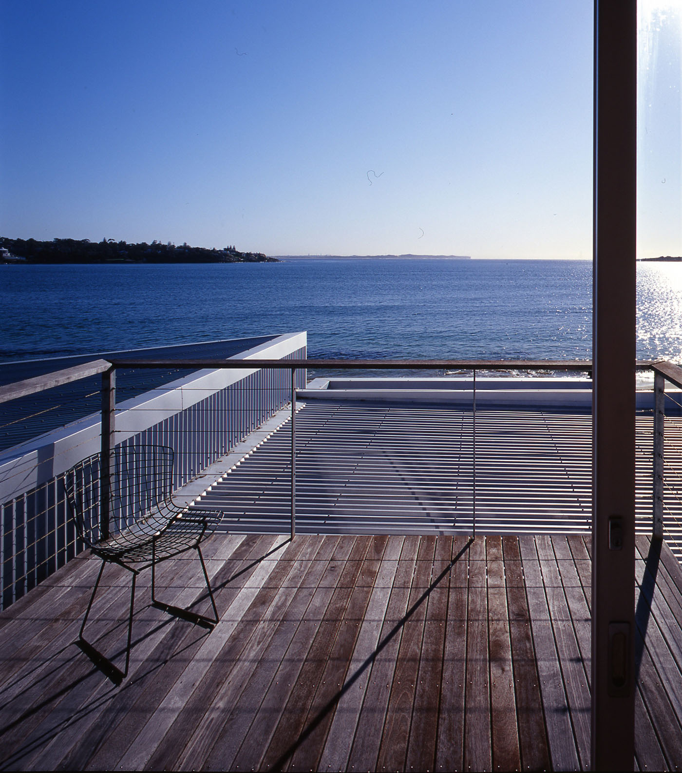 Bundeena Beach House by Sydney award winning residential architecture firm Sam Crawford Architects. View from timber deck to open beach.