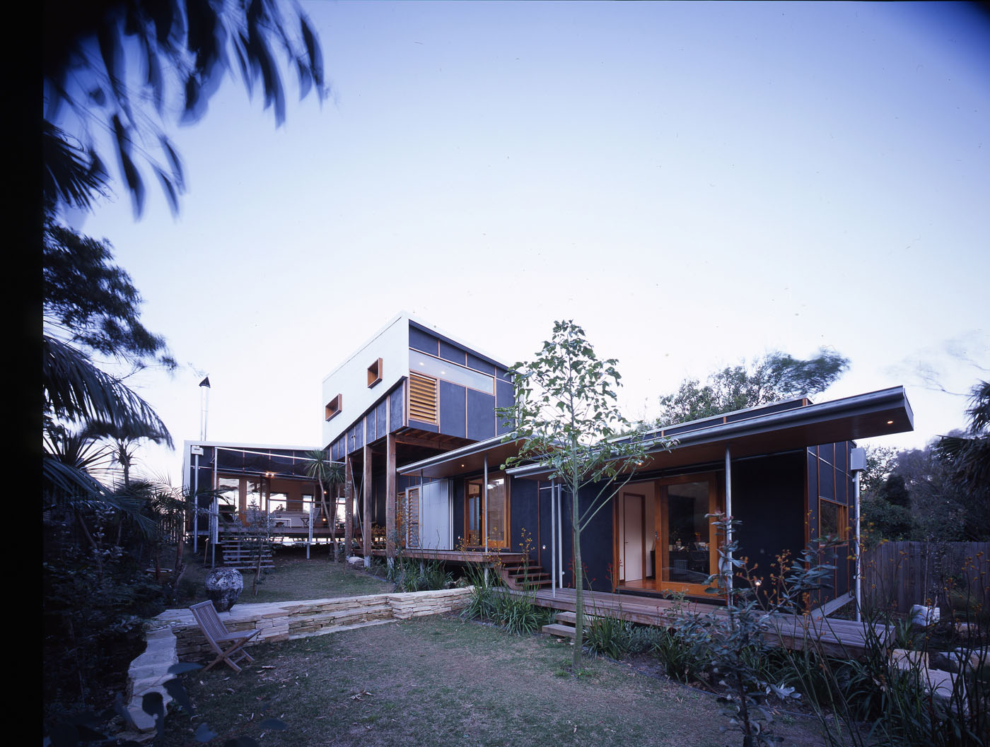 Bundeena Beach House by Sydney award winning residential architecture firm Sam Crawford Architects. View from garden to raised open deck.
