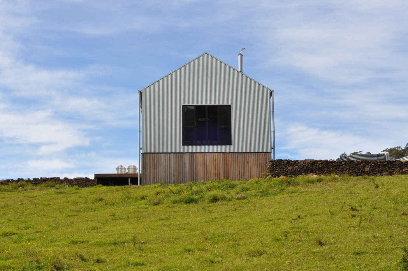 Gloucester Farmhouse by award winning residential architecture firm Sam Crawford Architects. Front façade of timber boards and corrugated steel.