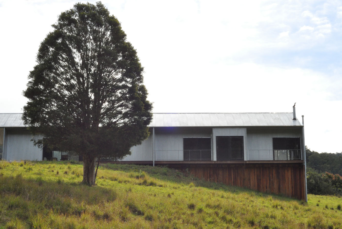 Gloucester Farmhouse by award winning residential architecture firm Sam Crawford Architects. Side view of the building sitting in the hills.
