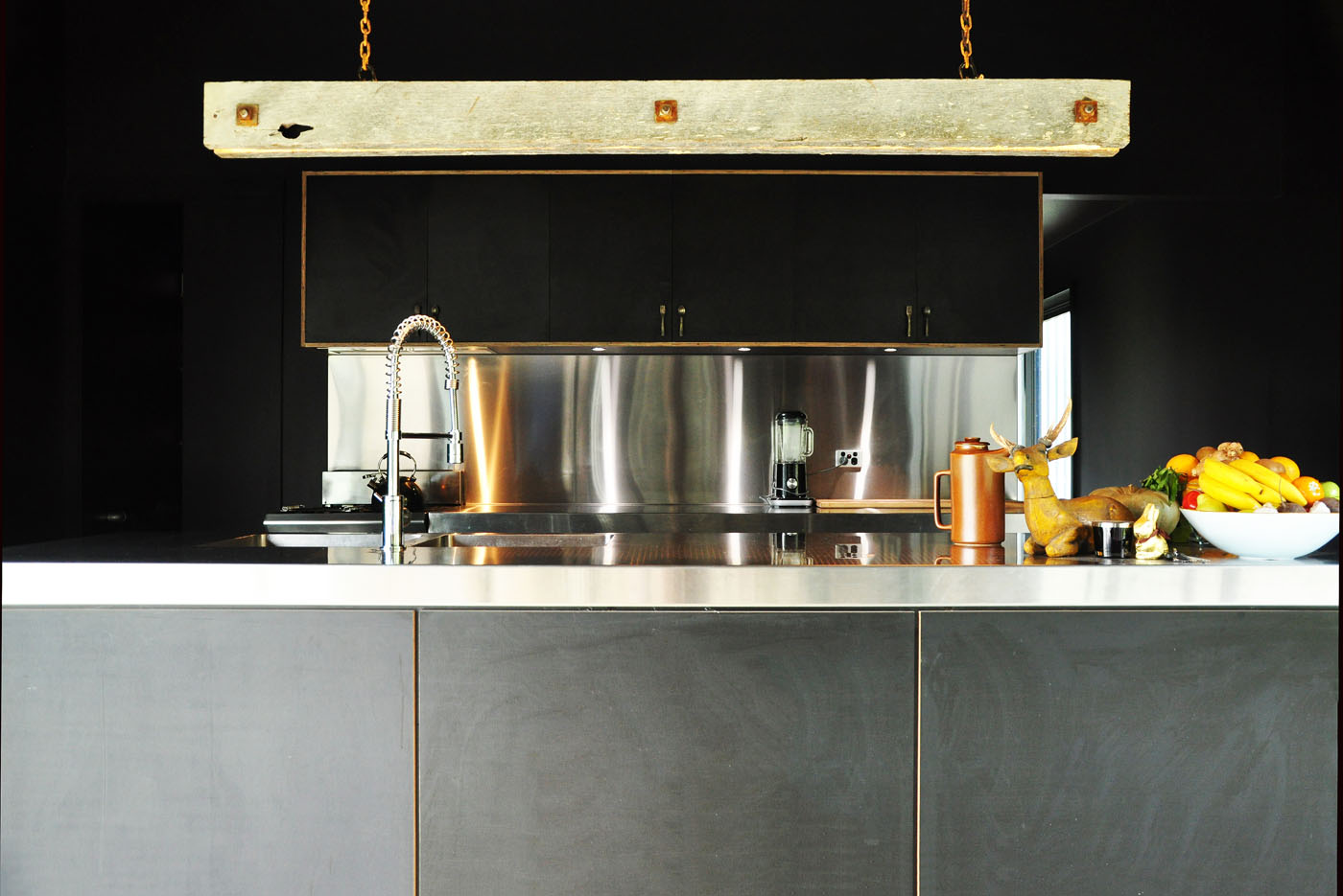 Gloucester Farmhouse by award winning residential architecture firm Sam Crawford Architects. Detail of industrial kitchen with stainless steel benchtop, black painted plywood and raw timber suspended light