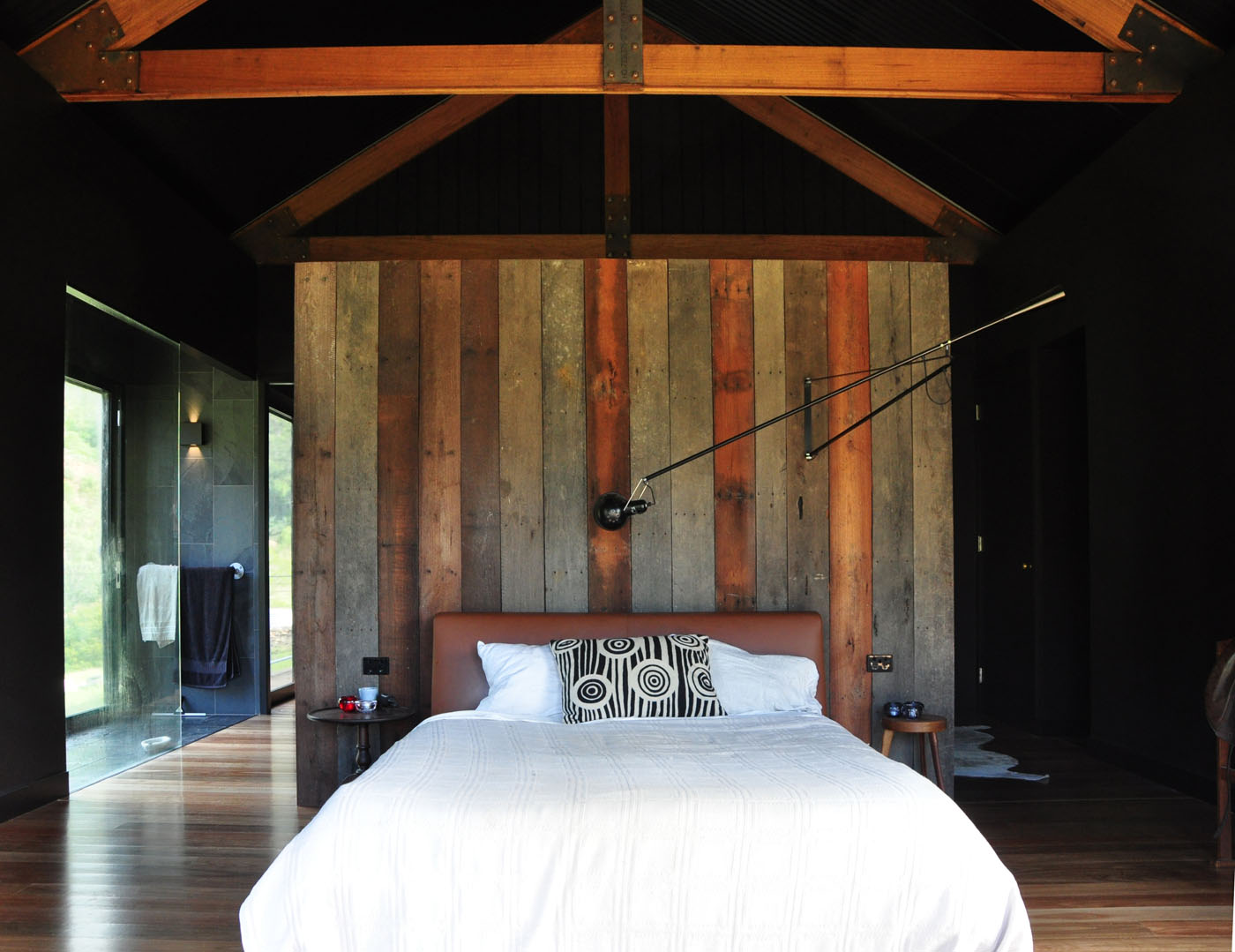 Gloucester Farmhouse by award winning residential architecture firm Sam Crawford Architects. Open plan bedroom with exposed structures and raw material palette