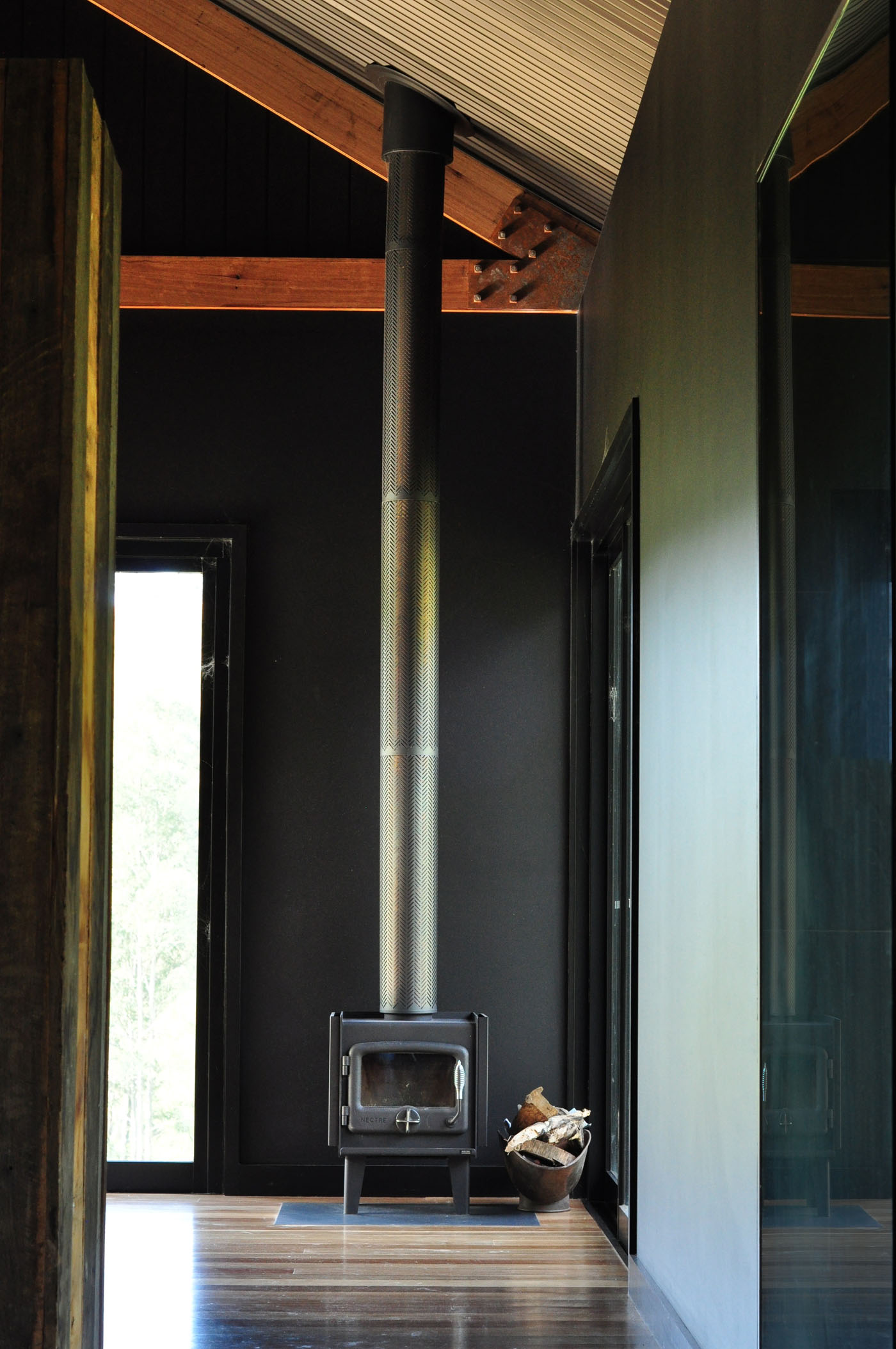 Gloucester Farmhouse by award winning residential architecture firm Sam Crawford Architects. Black powder coated and stainless steel fireplace adds to the industrial feel of the interior.