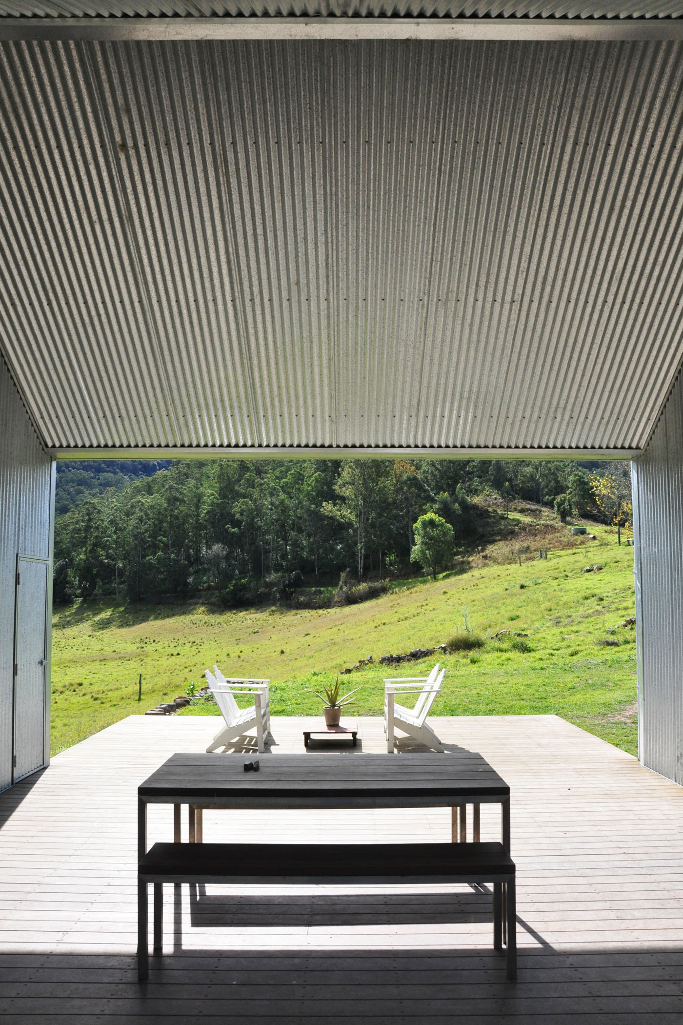 Gloucester Farmhouse by award winning residential architecture firm Sam Crawford Architects. View to the hills landscape from the intermediate deck