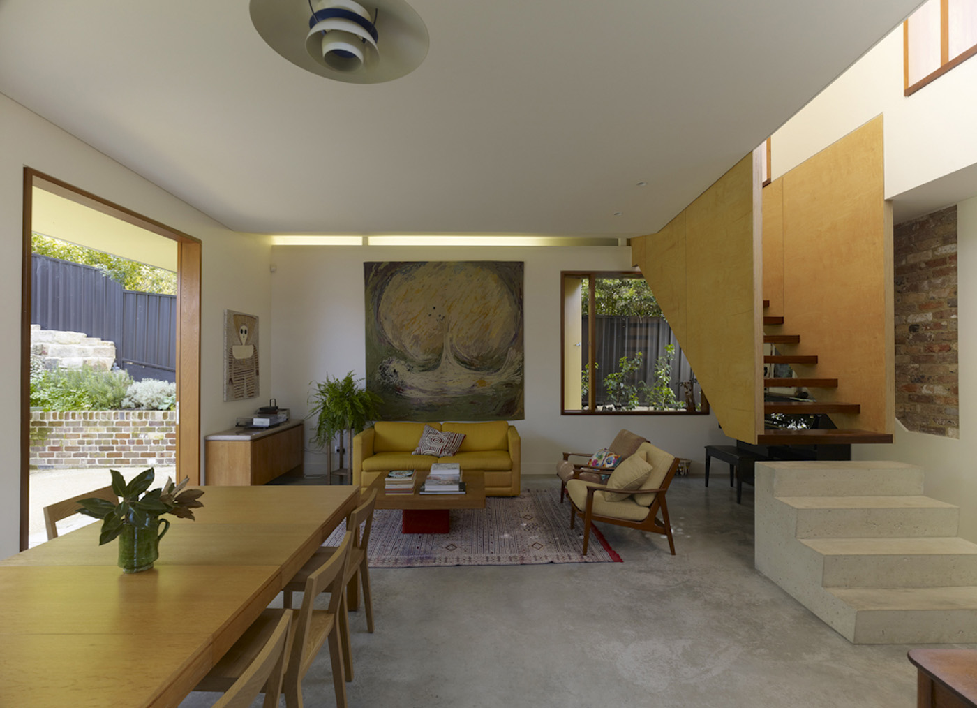 Campbell House by award winning Sydney residential architecture firm Sam Crawford Architects. View to open living area with concrete, brick and timber as main material palette.