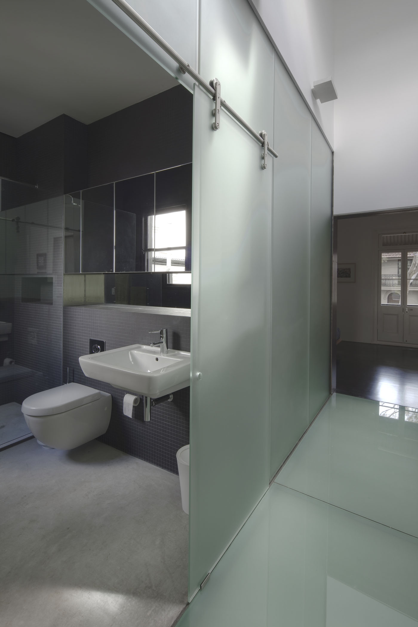 Newtown Terrace by award winning Sydney firm Sam Crawford Architects. Ambient bathroom with raw concrete floor and sliding frosted glass doors.