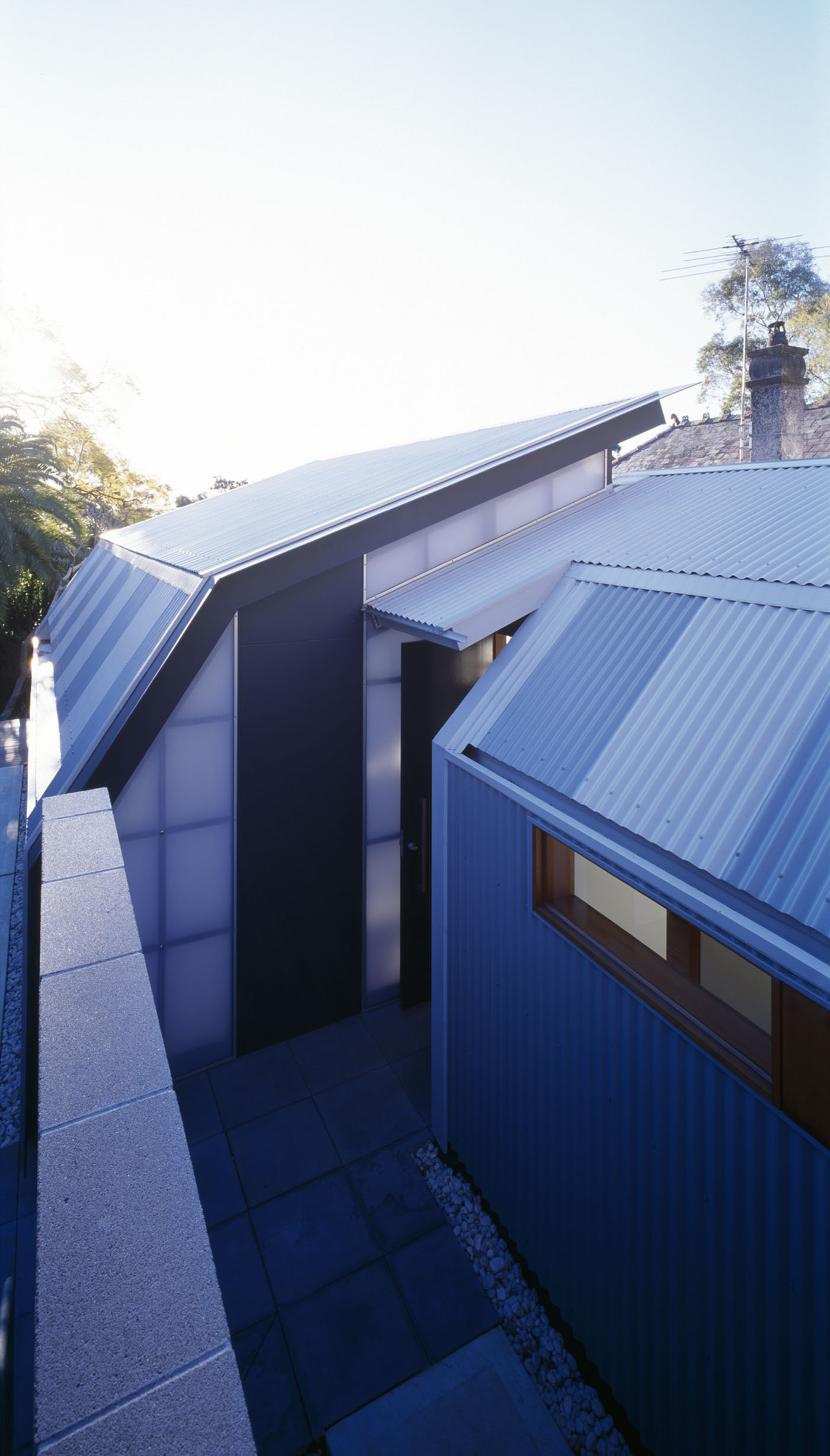 Wave House by Sydney award winning residential architecture firm Sam Crawford Architects. View of folded metal deck roof over new house addition from side entry.