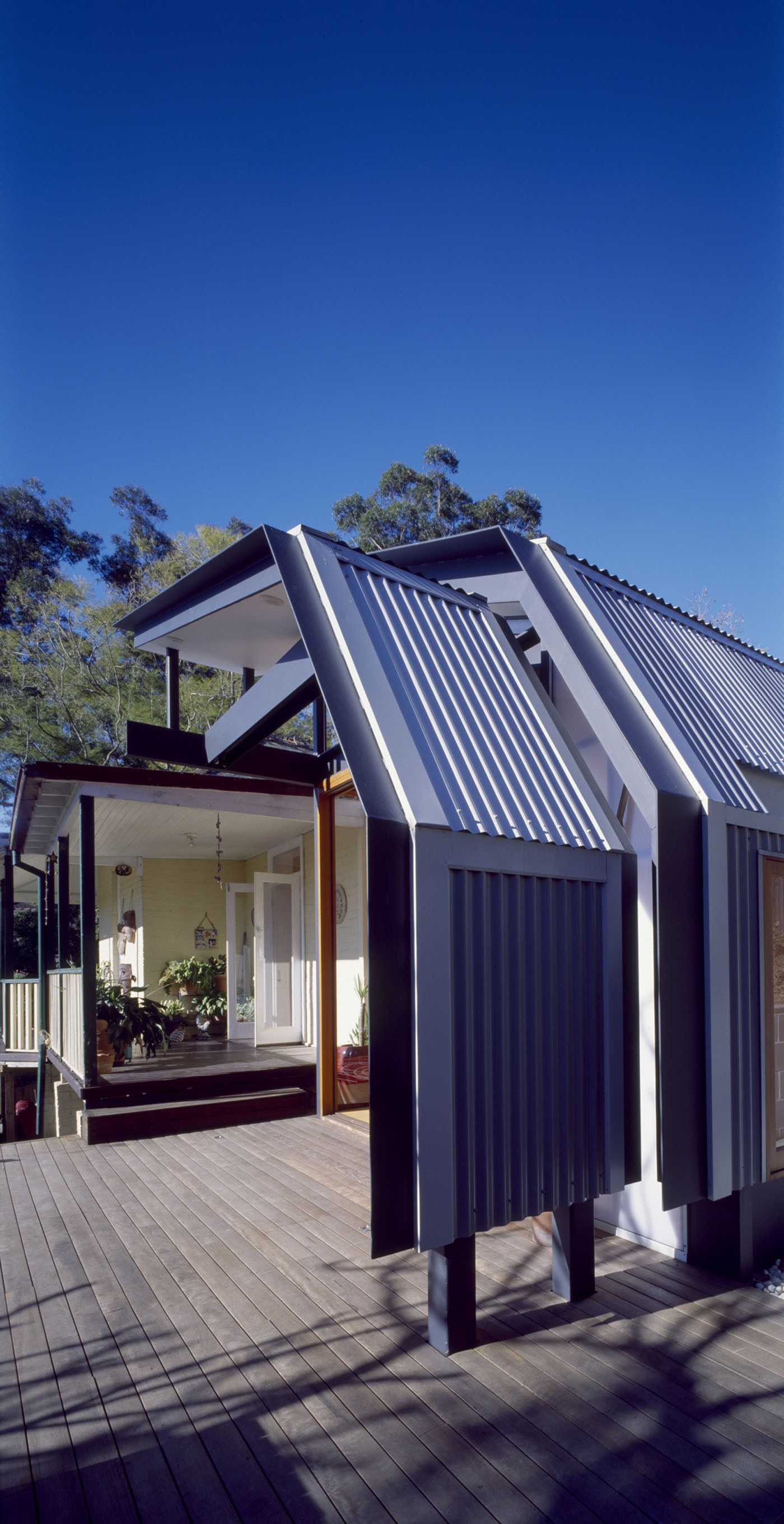 Wave House by Sydney award winning residential architecture firm Sam Crawford Architects. Folded metal deck roof provides shading in summer and allows sunlight penetration in winter.