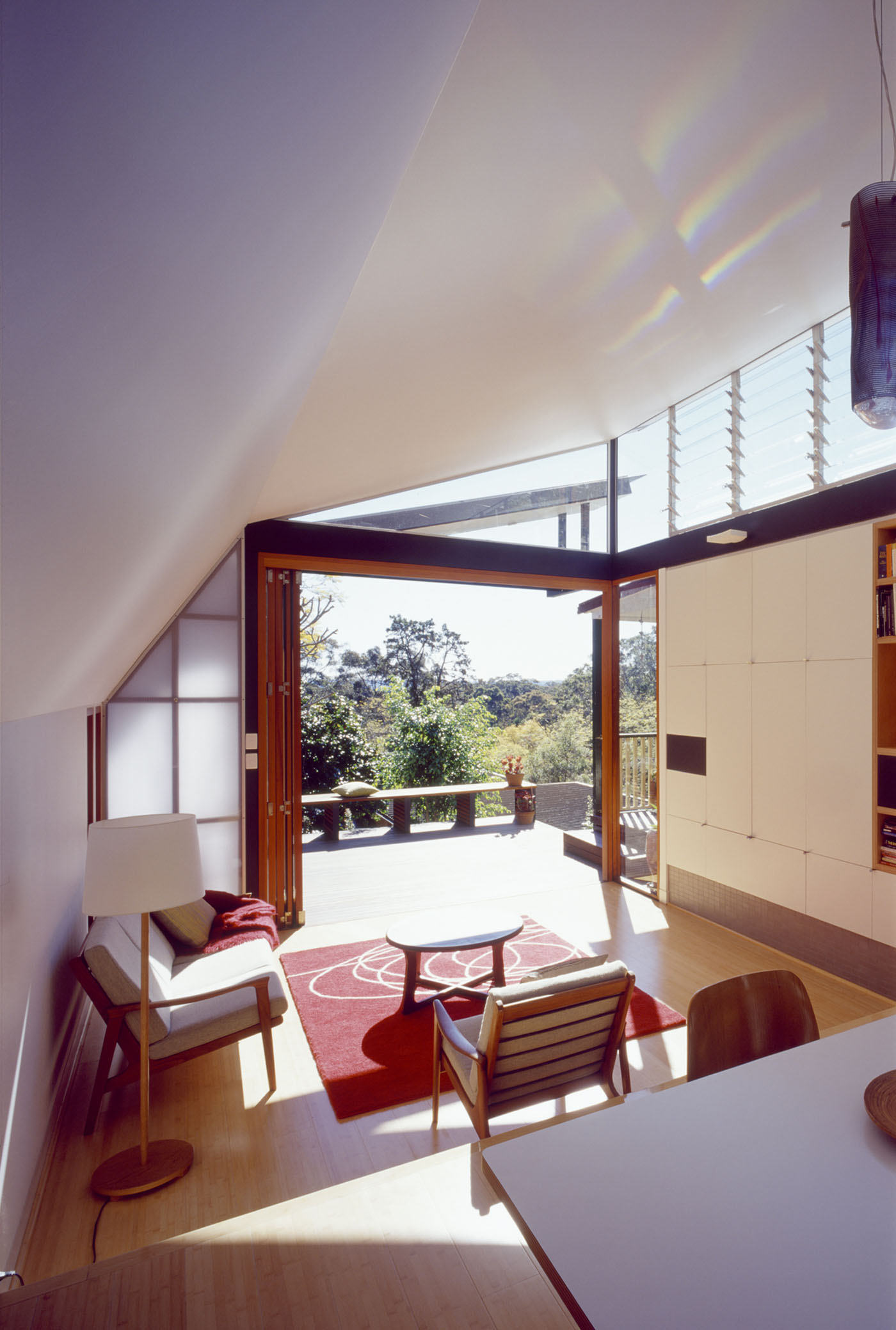 Wave House by Sydney award winning residential architecture firm Sam Crawford Architects. Bright living room looking out to green valley and distant mountain views.