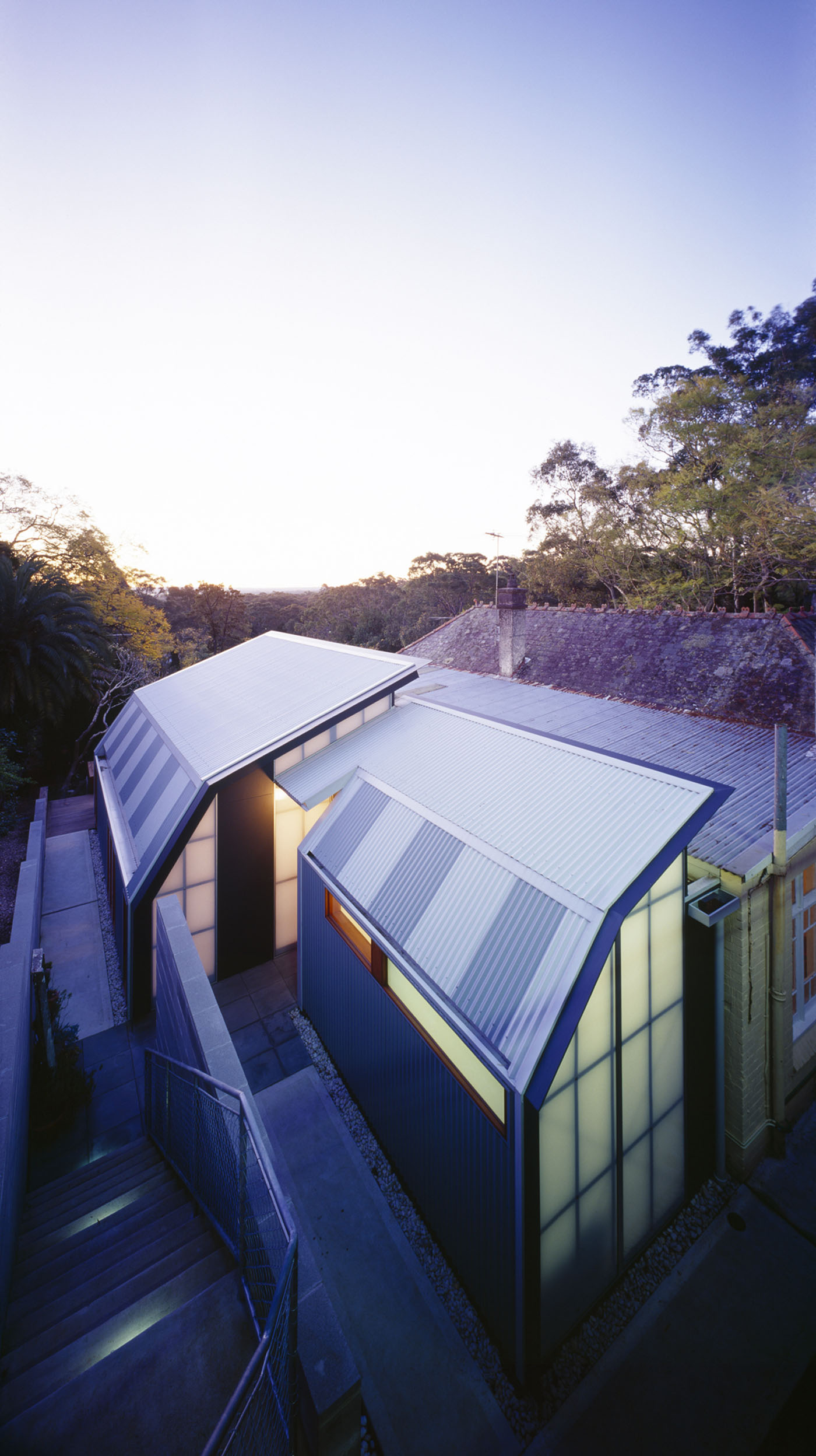 Wave House by Sydney award winning residential architecture firm Sam Crawford Architects. View to house at twilight. Light filtered through translucent polycarbonate sheets