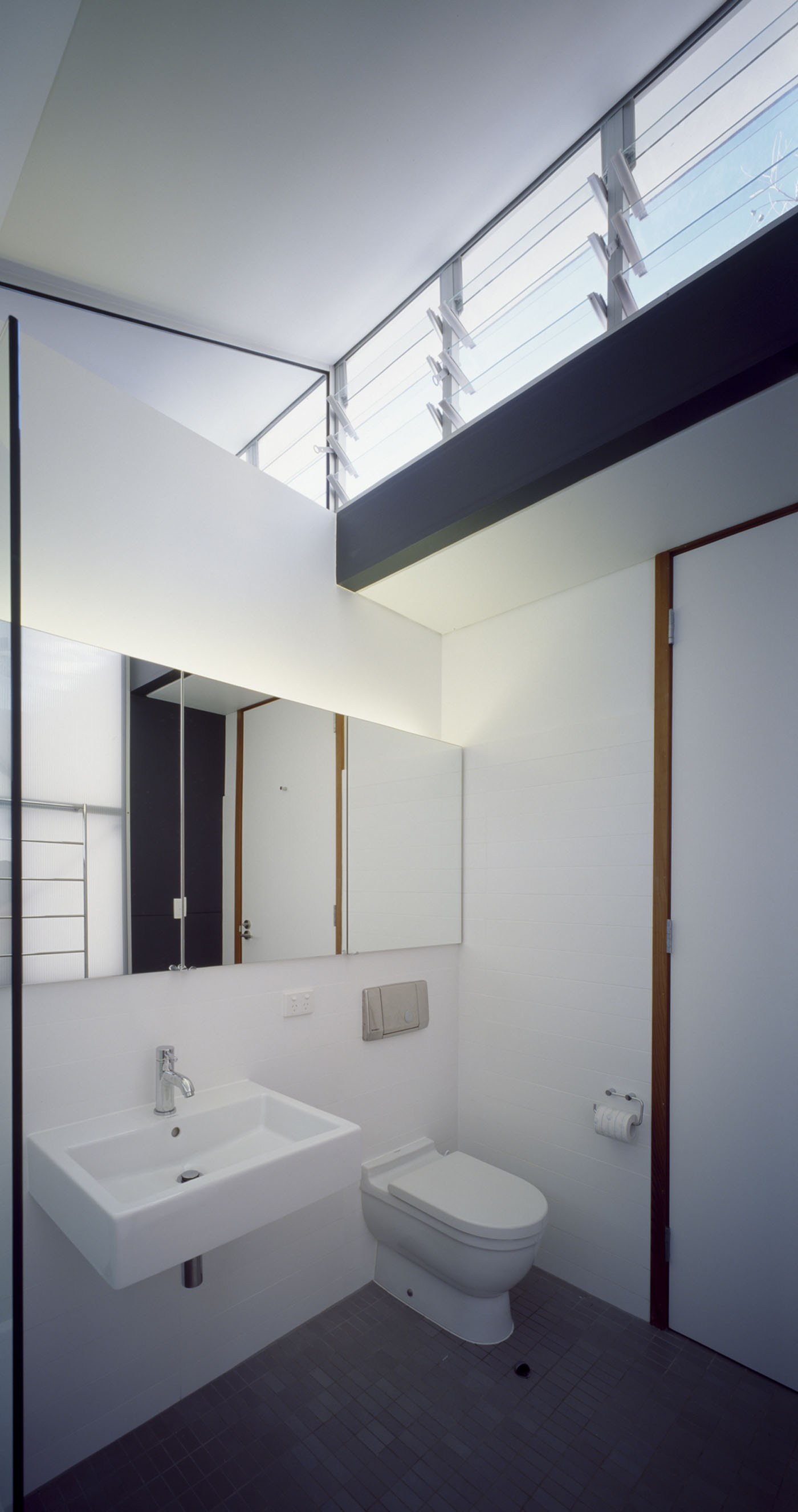 Wave House by Sydney award winning residential architecture firm Sam Crawford Architects. Simple high ceiling bathroom with glass louvers to provide ventilation