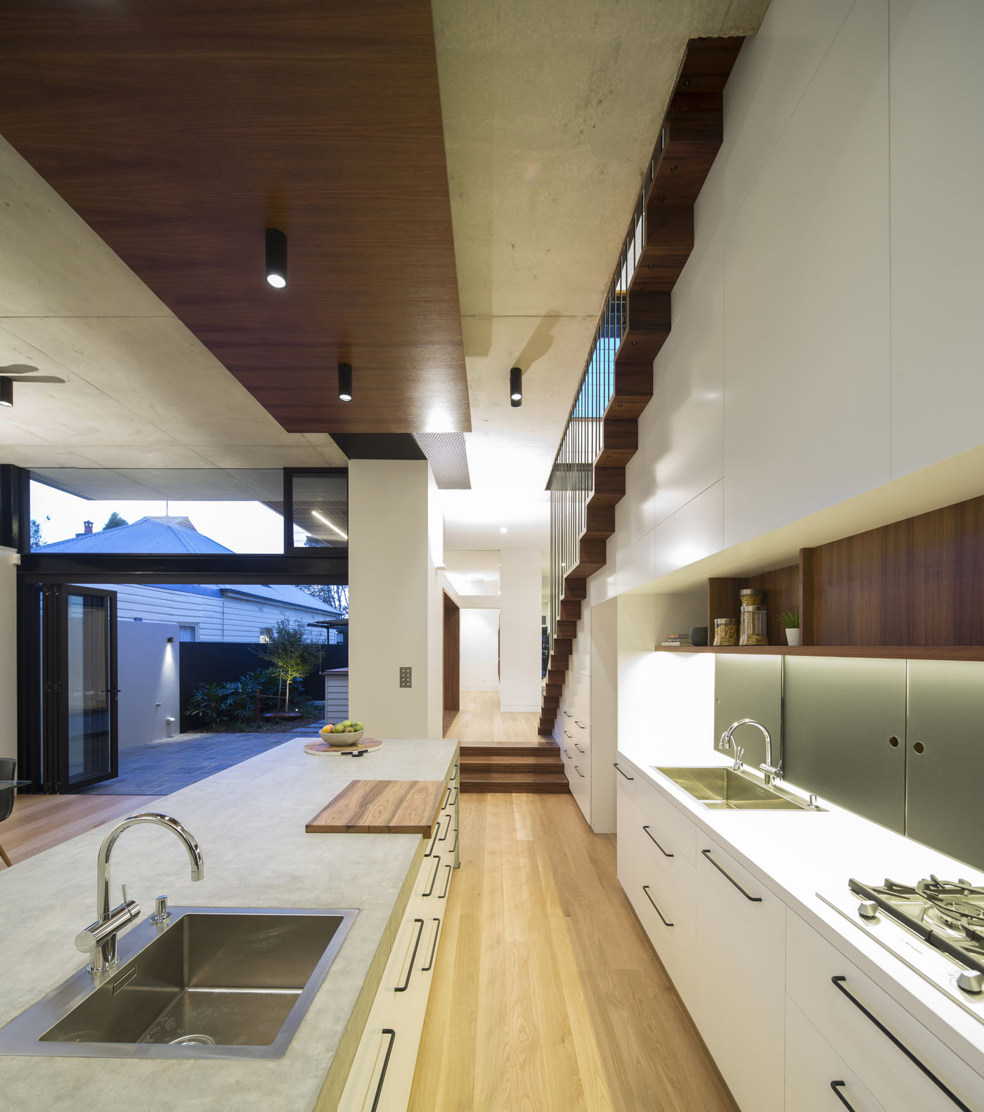 Sheppard Wilson House by Sydney award winning residential architecture office Sam Crawford Architects. American oak flooring against white joinery and concrete island