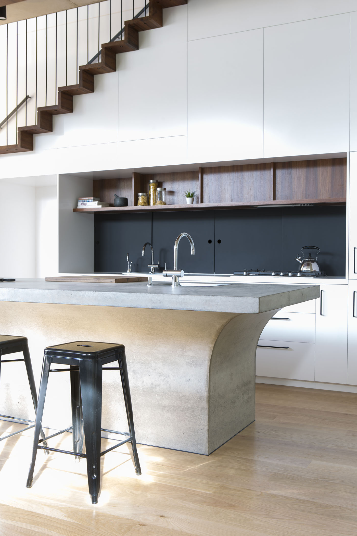 Sheppard Wilson House by Sydney award winning residential architecture office Sam Crawford Architects. Bespoke kitchen featuring curvilinear concrete island and timber joinery