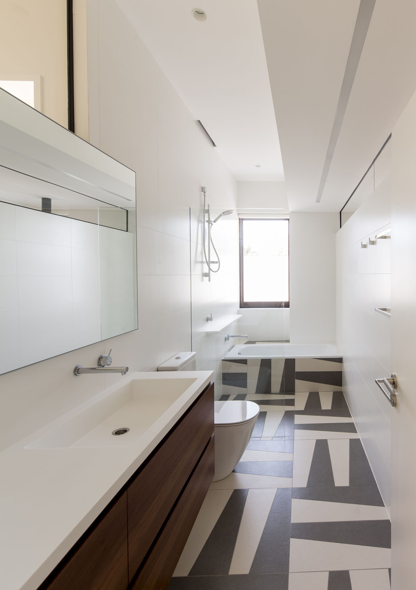 Sheppard Wilson House by Sydney award winning residential architecture office Sam Crawford Architects. Bespoke bathroom featuring black and white geometric floor tiles