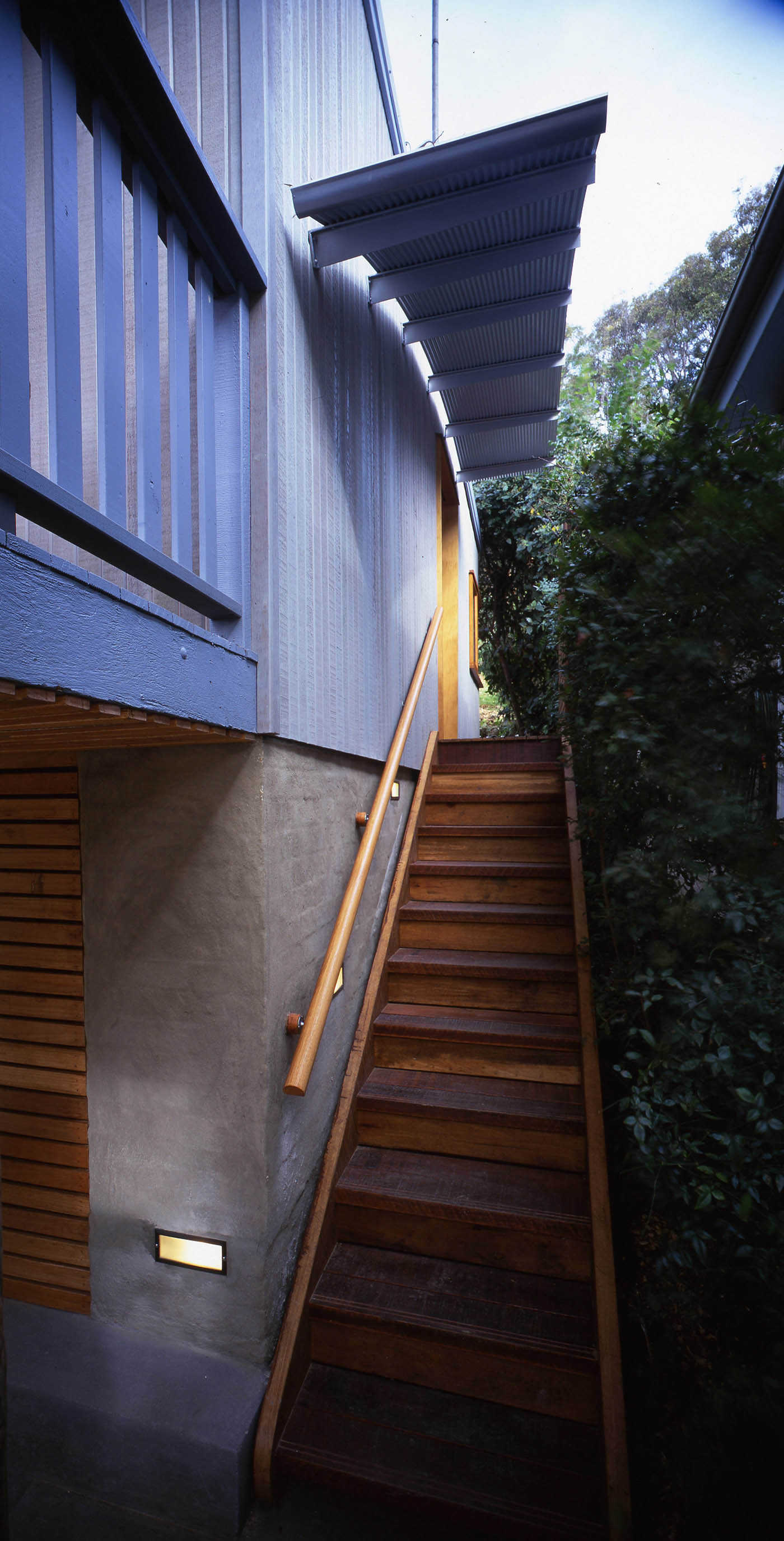 Avalon Beach House by Sydney award winning residential architecture firm Sam Crawford Architects. Timber stairs to upper level with protruding corrugated roof shading
