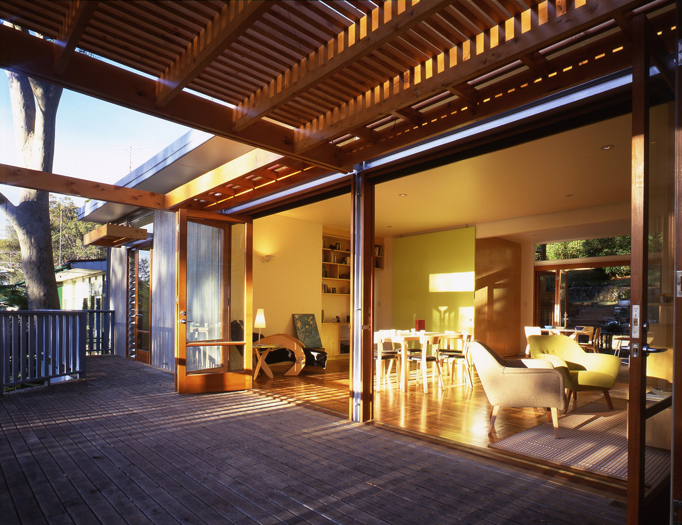 Avalon Beach House by Sydney award winning residential architecture firm Sam Crawford Architects. Renovated deck with timber slat pergola and open interior connected to its surroundings.