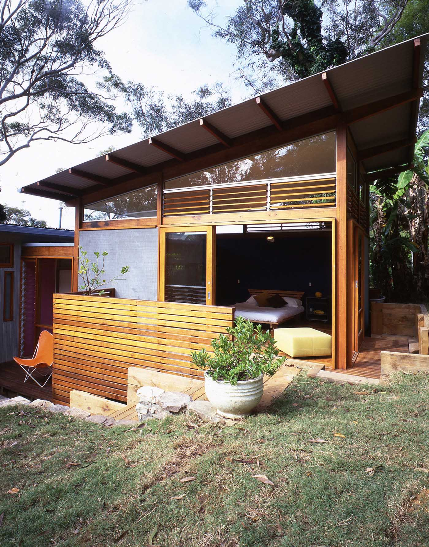 Avalon Beach House by Sydney award winning residential architecture firm Sam Crawford Architects. View from garden to timber bedroom with slanted corrugated roof