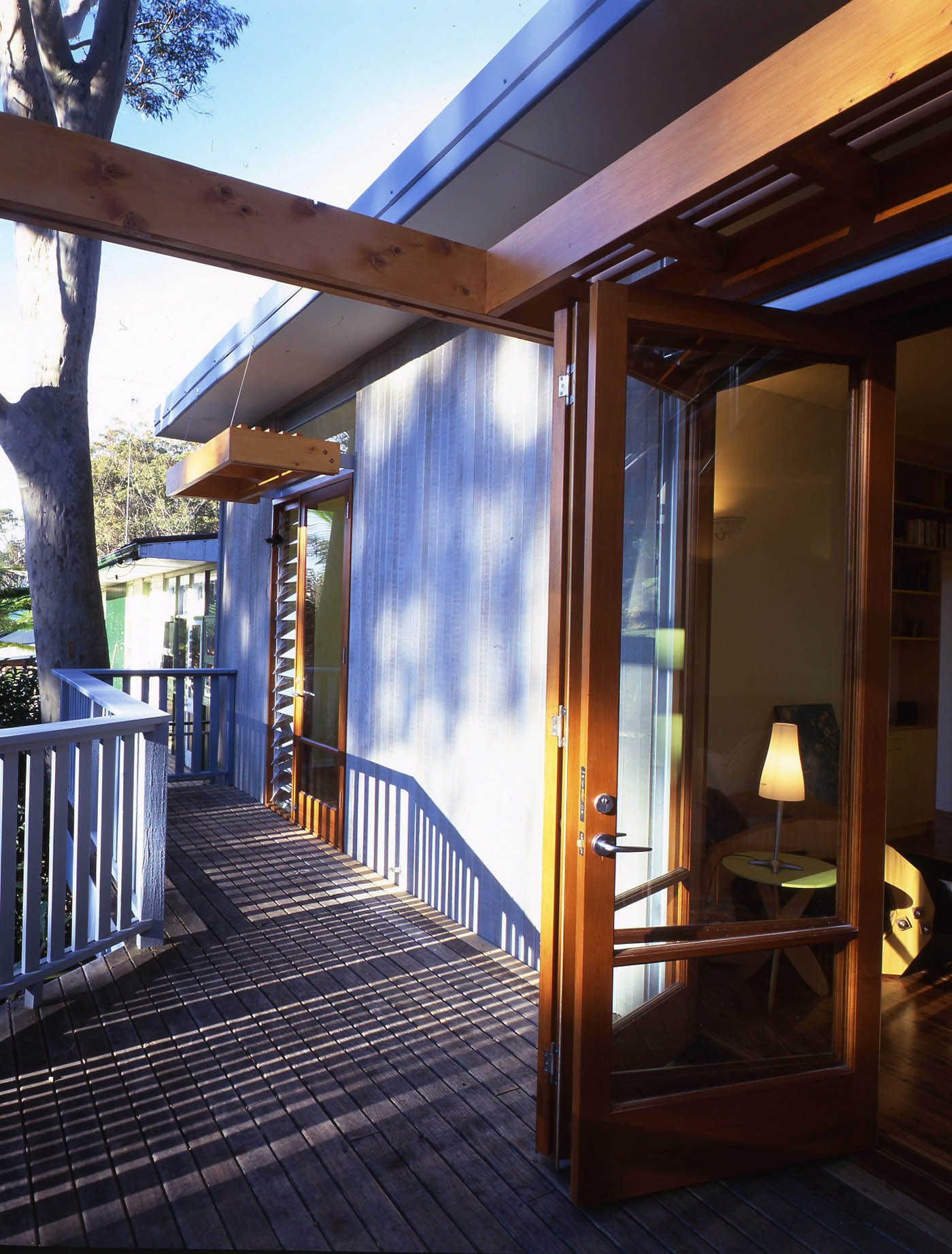Avalon Beach House by Sydney award winning residential architecture firm Sam Crawford Architects. Dappled light from surrounding trees on timber deck and wall.