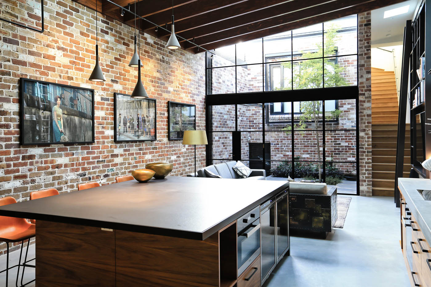 Darlinghurst Warehouse by award winning Sydney residential architecture firm Sam Crawford Architects. Rich material palette provides characteristic to the open living and dining space, looking out to a light-filled courtyard.