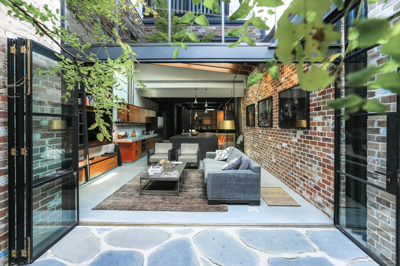Darlinghurst Warehouse by award winning Sydney residential architecture firm Sam Crawford Architects. The transition of grey stone floor provide a continuity from the interior to the courtyard