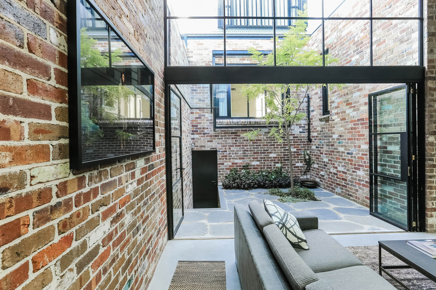 Darlinghurst Warehouse by Sydney award winning residential architecture office Sam Crawford Architects. Recycled brick, black steel, timber joinery and concrete floor form a palette that combines heavy durability with warmth.