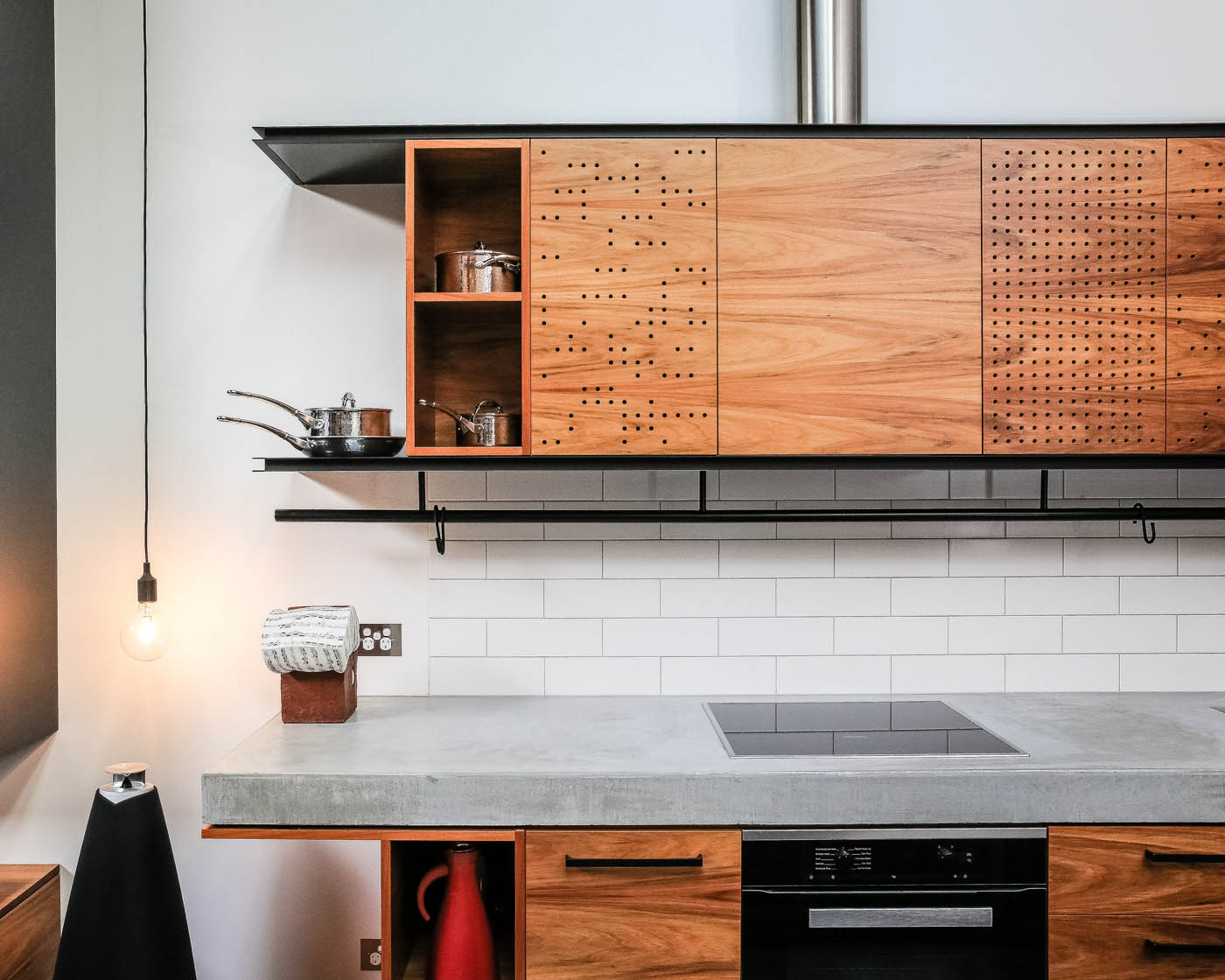 Darlinghurst Warehouse by Sydney award winning residential architecture office Sam Crawford Architects. Detail of perforated timber kitchen joinery, black steel and grey stone.