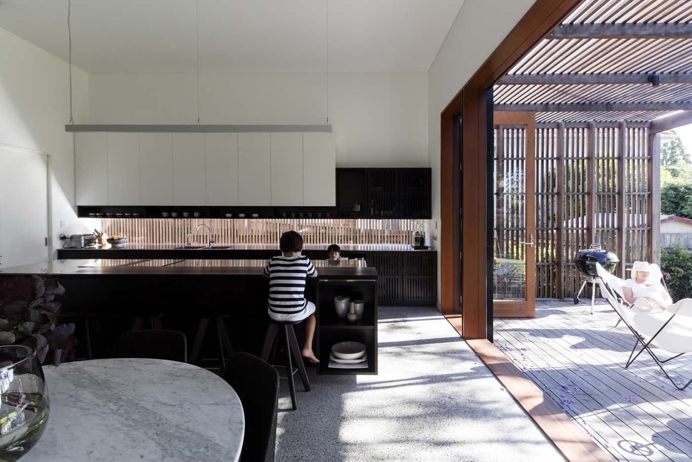 Sung Dobson house by Sam Crawford Architects, Sydney. Kitchen in dark stained timber, white and stainless steel.