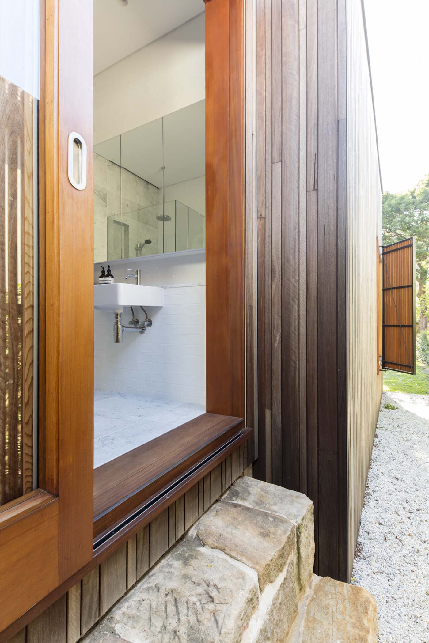 Sung Dobson house by Sam Crawford Architects, Sydney. Bathroom and sandstone step leads outdoors.