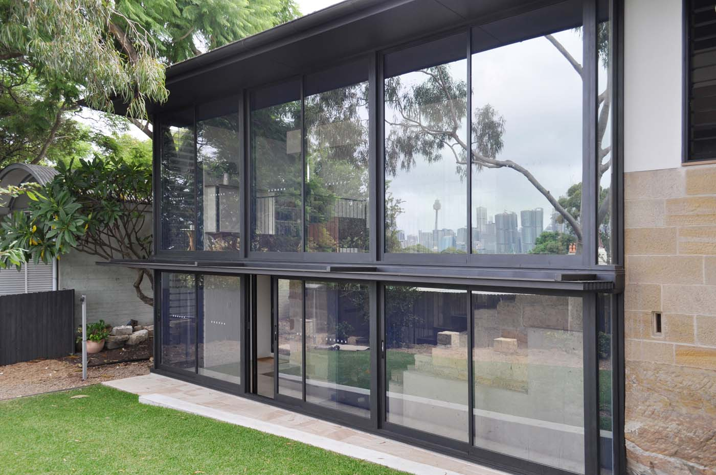 Balmain Cottage by award winning Sydney firm Sam Crawford Architects. Large glass façade reflect view to the city blending with greenery