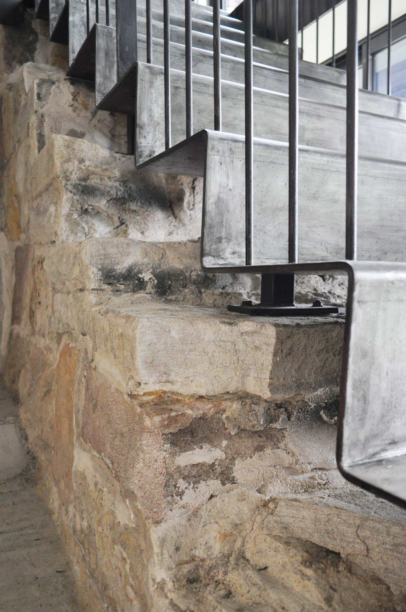Balmain Cottage by award winning Sydney firm Sam Crawford Architects. Detail of modern raw steel staircase against old sandstone steps