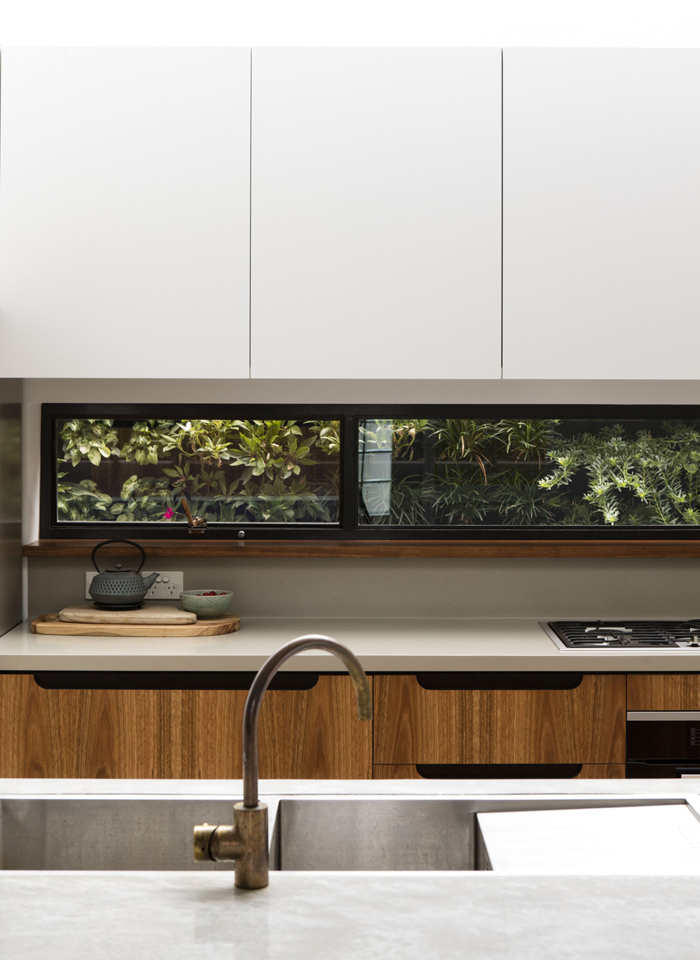 Conway Atkins House in Dover Heights by Sydney architect Sam Crawford Architect. The kitchen features a picture window looking out onto a green courtyard.
