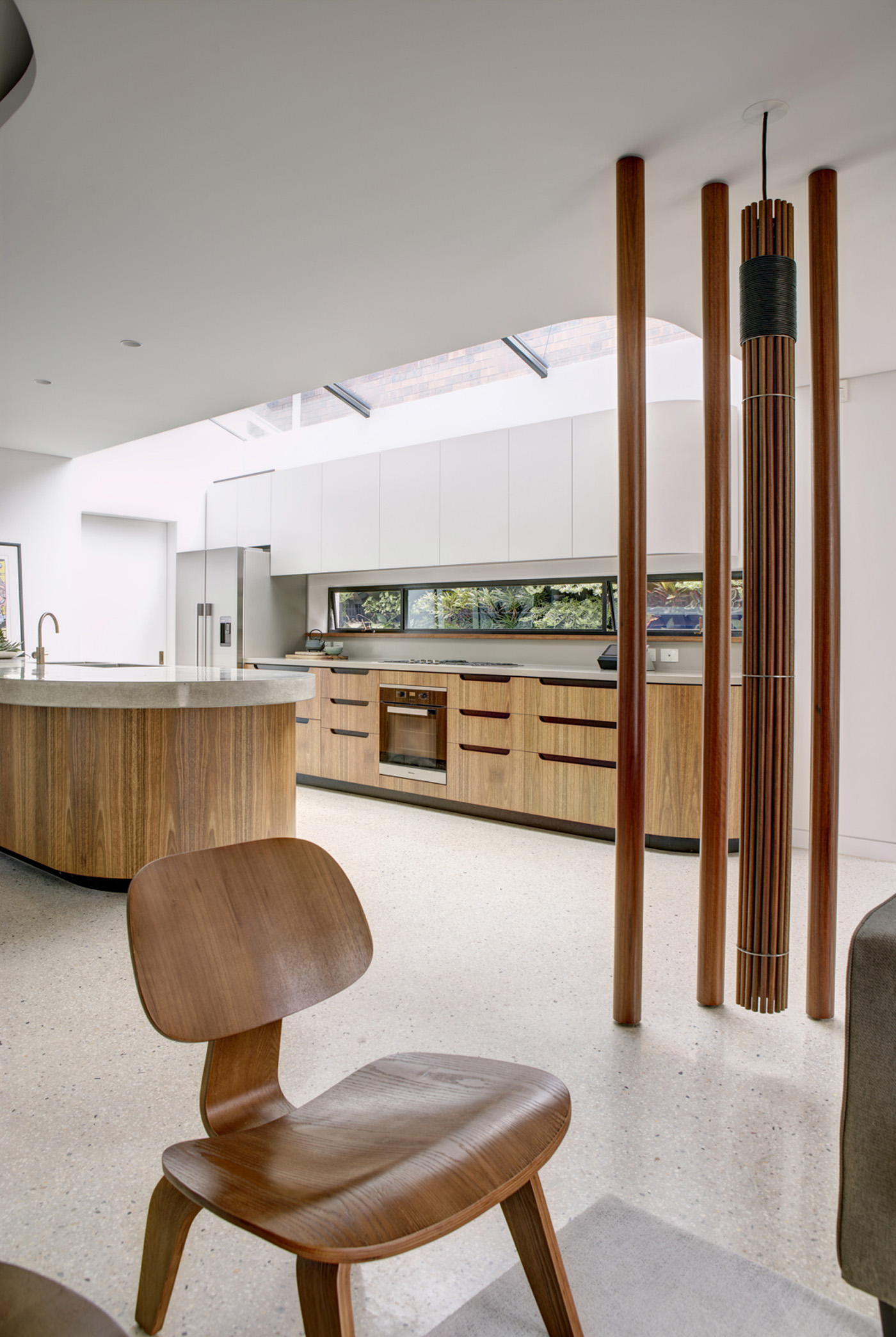 Dover Heights Pendants by award winning Sydney firm Sam Crawford Architects. View to light-filled kitchen with round posts and custom made pendant light.