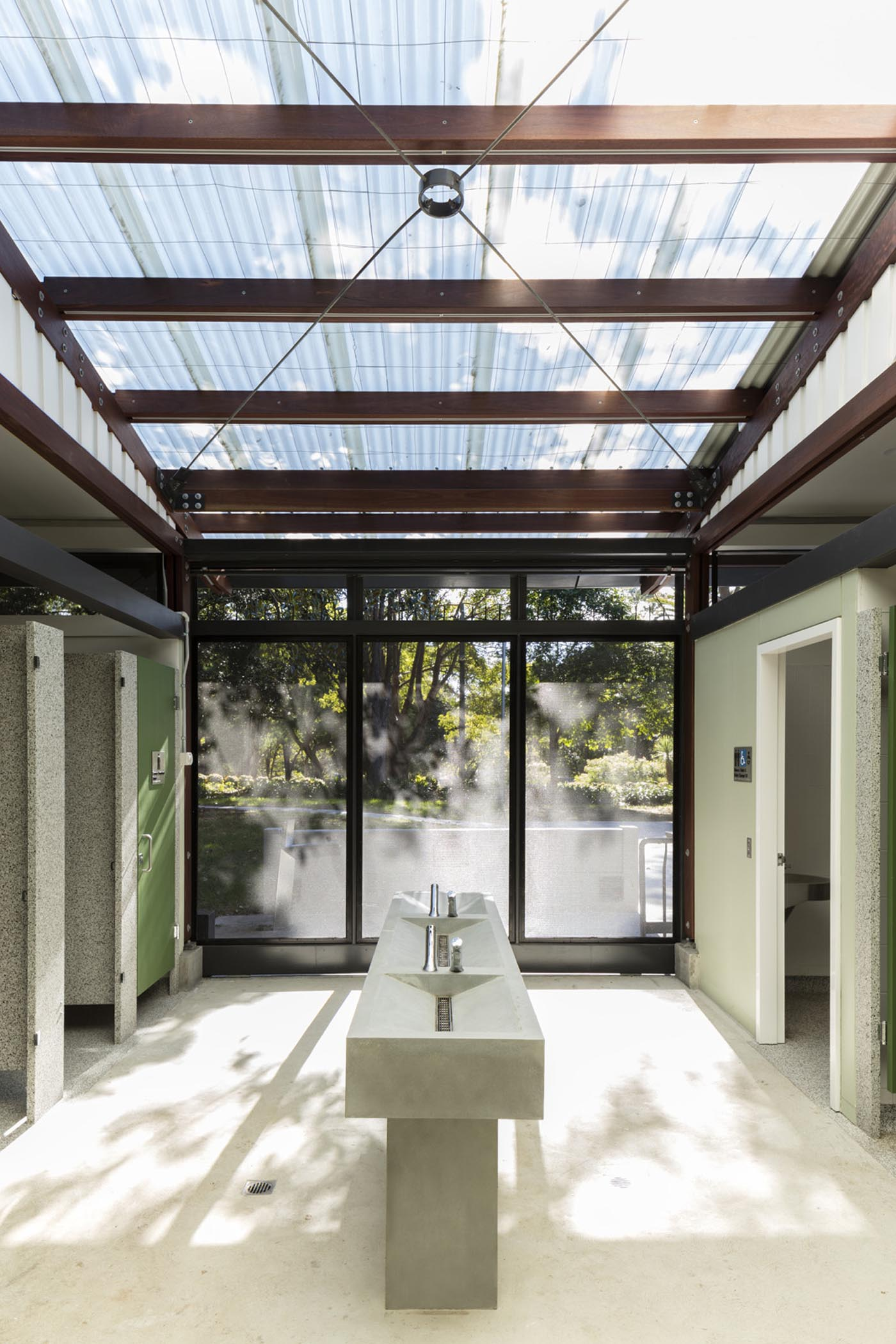 Cabarita Park Conservatory by award winning public architectural firm Sam Crawford Architects. Light filtered through translucent corrugated roof to concrete wash basin